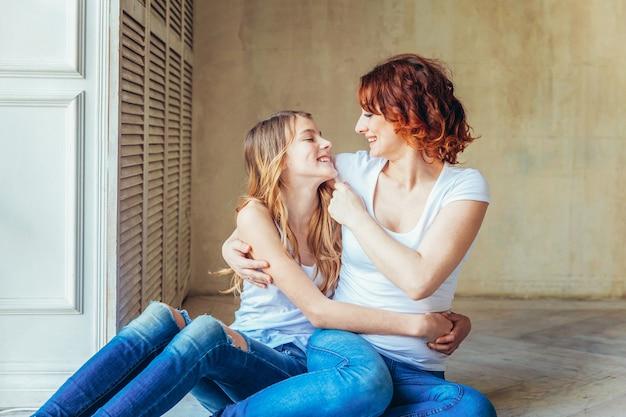 Jonge moeder die haar kind omhelst. vrouw en tienermeisje ontspannen in witte slaapkamer in de buurt van grijze muur binnenshuis. gelukkige familie thuis. jonge moeder speelt met haar dochter.