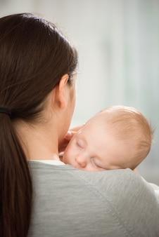 Jonge moeder die haar pasgeboren kind houdt.