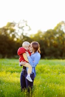 Jonge moeder die haar weinig zoon kust tijdens gang op het bloemengebied