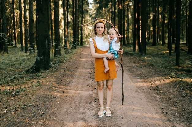 Jonge moeder die haar zoon met stok in het bos houdt