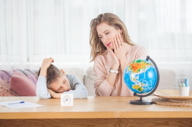 Jonge moeder die haar zoontje thuis onderwijst. moeder en haar kind studeren aardrijkskunde binnenshuis
