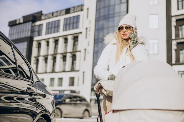 Jonge moeder die in de winter met haar pasgeboren baby in de kinderwagen loopt