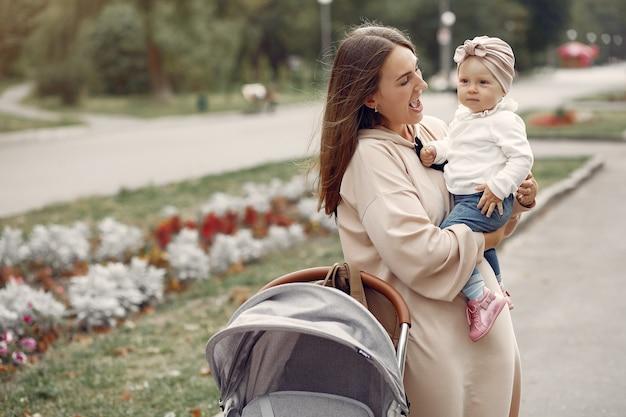 Jonge moeder die in een de herfstpark loopt met vervoer