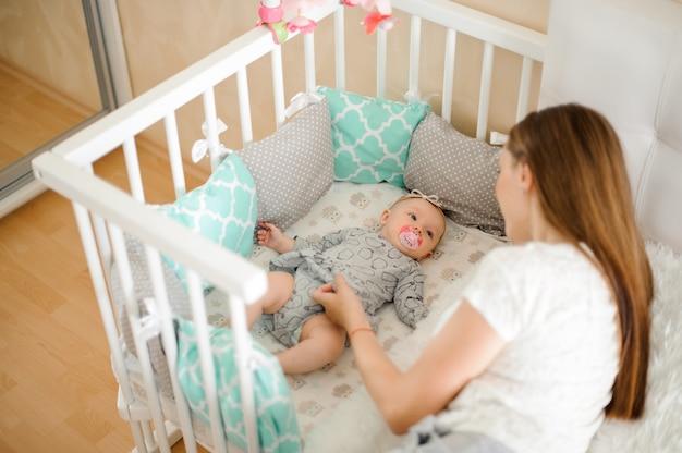 Jonge moeder die klein klein pasgeboren babymeisje in bed sust
