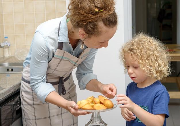 Jonge moeder die koekjes geeft aan haar kind