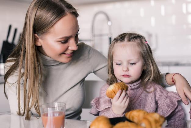 Jonge moeder die meisje het drinken sap kijken terwijl zij samen ontbijt hebben