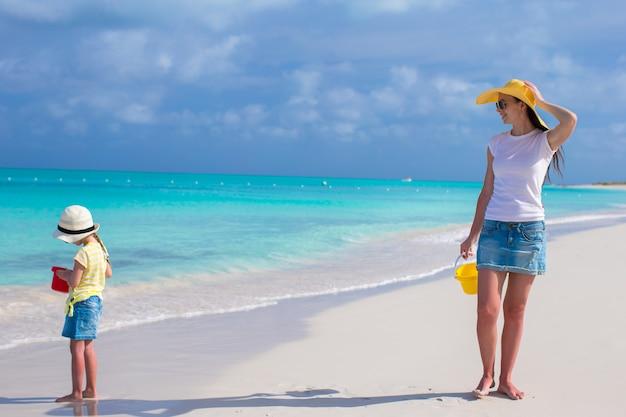 Jonge moeder die met haar dochter tijdens hun caraïbische vakantie loopt