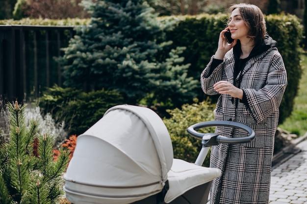 Jonge moeder die met kinderwagen in park loopt en op de telefoon spreekt
