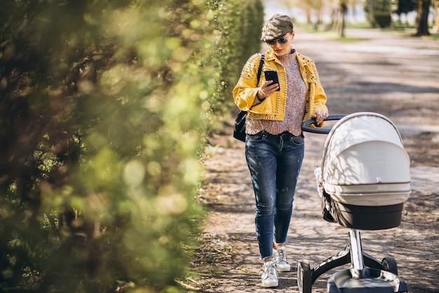Jonge moeder die met kinderwagen in park loopt en telefoon met behulp van