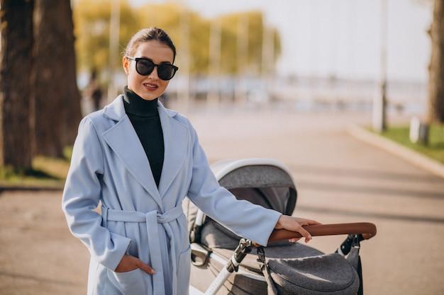 Jonge moeder die met kinderwagen in park loopt