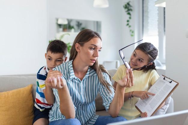 Jonge moeder die met laptop werkt terwijl haar zoon en dochter in de woonkamer spelen. moeder probeert thuis te werken
