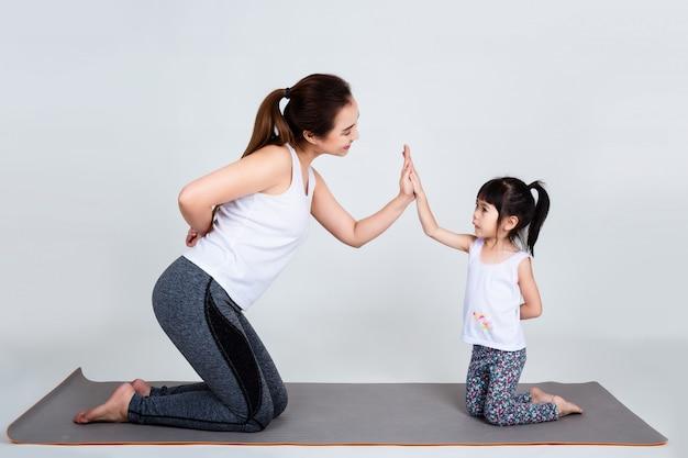 Jonge moeder die mooie dochter met gymnastiek opleidt
