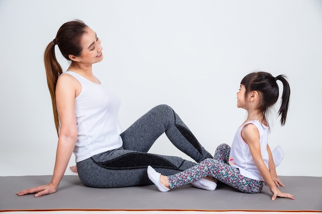 Jonge moeder die mooie dochter met yoga opleidt