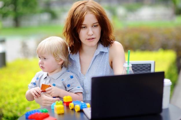 Jonge moeder die oh haar laptop werkt en haar droevige peuterzoon houdt