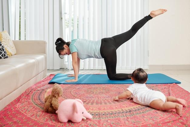 Jonge moeder die op yogamat uitoefent