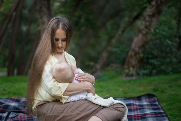 Jonge moeder die pasgeboren in park de borst geeft. moeder en baby zittend op picknickdeken