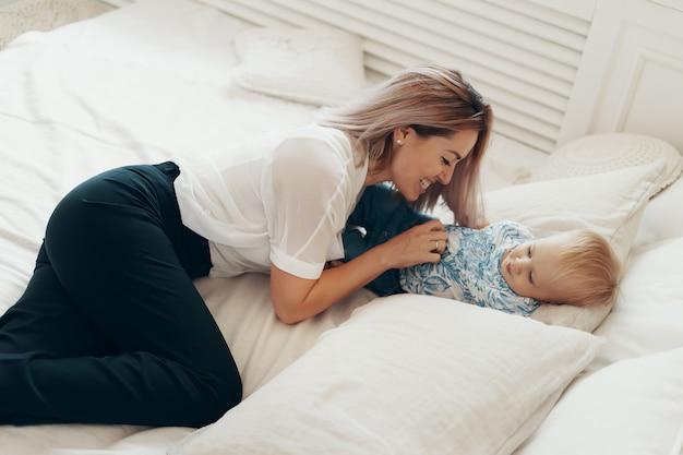 Jonge moeder die pret heeft die grappige actieve spelen met leuke kindzoon speelt in slaapkamer