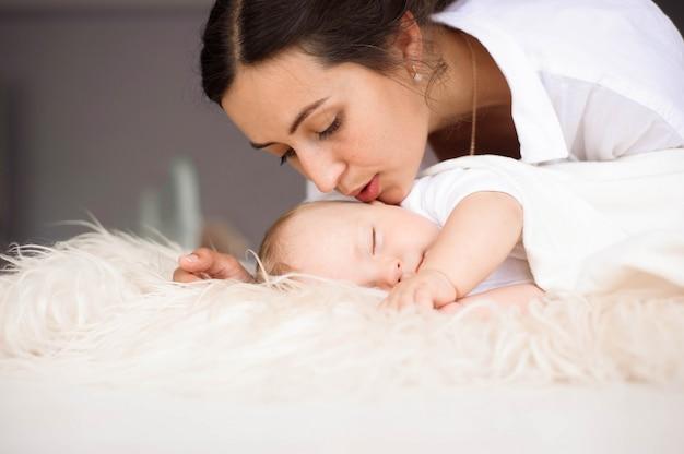 Jonge moeder, die teder haar pasgeboren babyjongen houdt