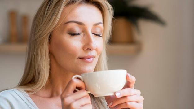 Jonge moeder die van de geur van koffie geniet