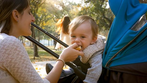 Jonge moeder die voedsel geeft aan haar schattige zoontje die in de kinderwagen zit in het auutmn park.
