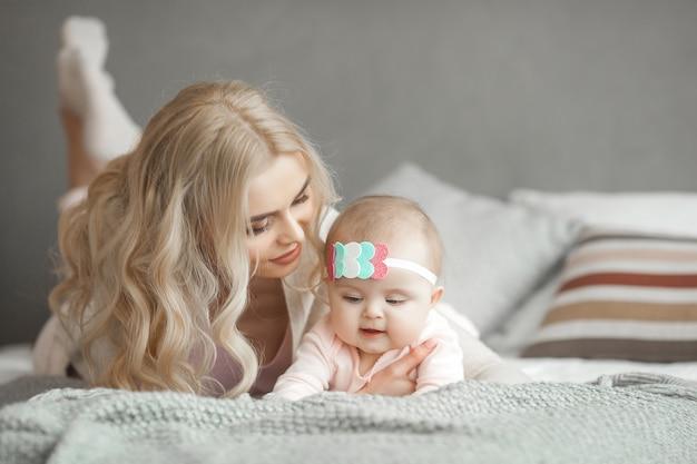 Jonge moeder die voor haar kleine babymeisje zorgt. mooie moeder en haar dochter binnenshuis in de slaapkamer. liefdevolle familie. aantrekkelijke moeder die haar kind houdt.