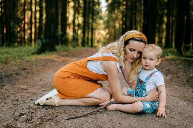 Jonge moeder die voor haar zoon in het bos zorgt