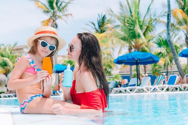 Jonge moeder die zonnebrandcrème toepast op jong geitjeneus in zwembad
