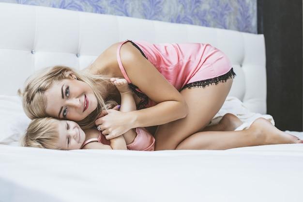 Jonge moeder dochter kleine baby in de slaapkamer, samen knuffelen en gelukkig