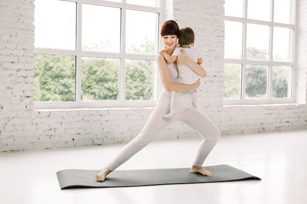 Jonge moeder doet fysieke yoga-oefeningen samen met haar baby. moeder met baby die gymnastiek en oefeningen doet