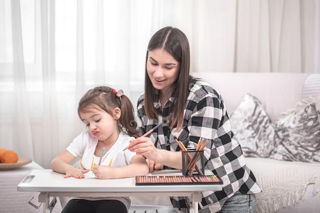 Jonge moeder doet huiswerk met haar schattige dochtertje. thuisonderwijs en onderwijsconcept.