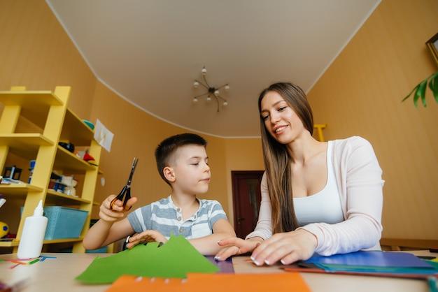 Jonge moeder doet huiswerk met haar zoon thuis. ouders en training