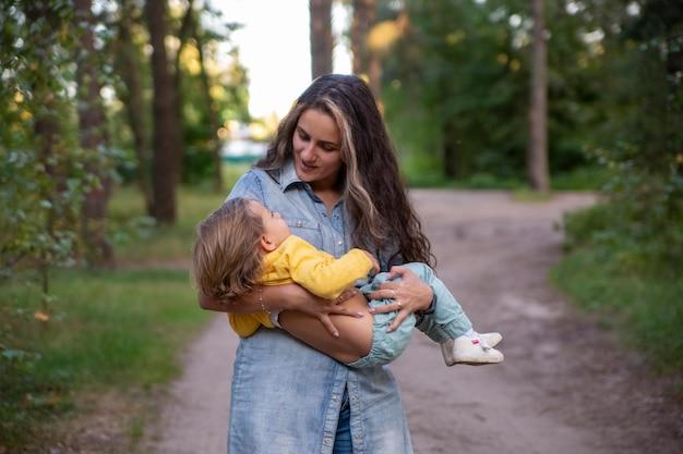 Jonge moeder draait met een baby in haar armen, gelukkige moeder danst met peuter op de achtergrond van
