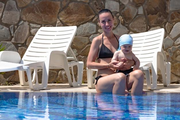 Jonge moeder, een mooi meisje en een kind in een opblaasbare kindercirkel, in een blauw zwembad op vakantie.
