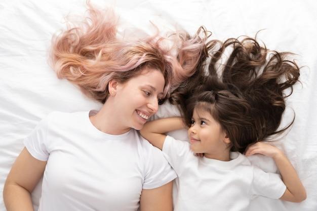 Jonge moeder en actieve dochtertje liggend in bed thuis, plezier.