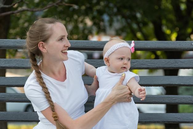 Jonge moeder en babymeisje zitten in park en glimlachen. gelukkig moederschap