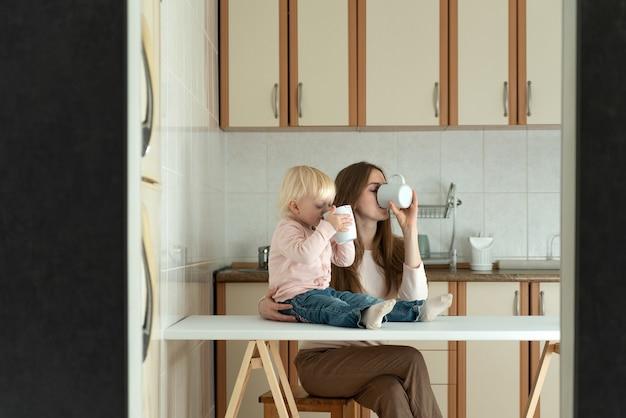 Jonge moeder en blonde peuter drankje uit mokken in de ochtend in de keuken. familie ontbijt.