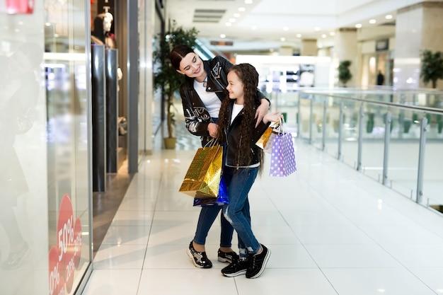 Jonge moeder en dochter die in een kledingwinkel winkelen
