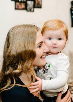 Jonge moeder en dochter die op hun laag zitten. gelukkig gezin. nieuwjaar concept. prettige kerstdagen en fijne feestdagen.