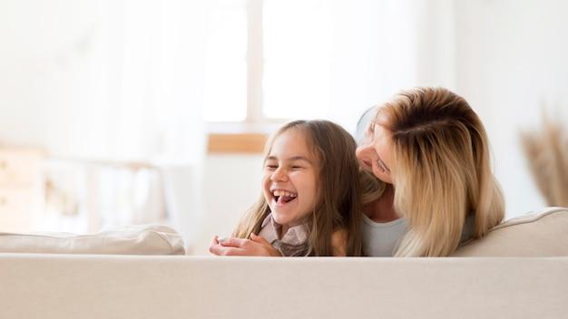 Jonge moeder en dochter die samen plezier hebben thuis