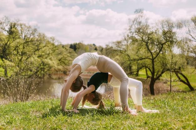 Jonge moeder en dochter die yoga in openlucht in het park doen