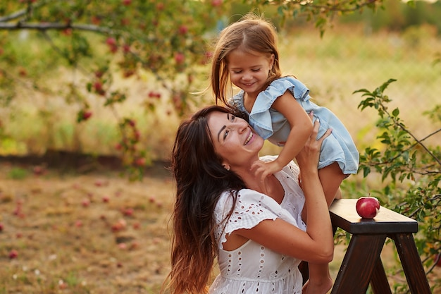 Jonge moeder en dochter in de oogst van de appelboomgaard