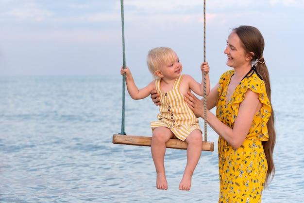 Jonge moeder en dochter in gele jurken tegen de zee. moeder rolt het kind op de schommel