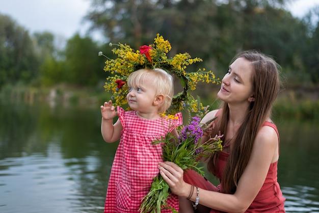 Jonge moeder en dochter in krans van bloemen op het meer. ivan kupala vakantie.