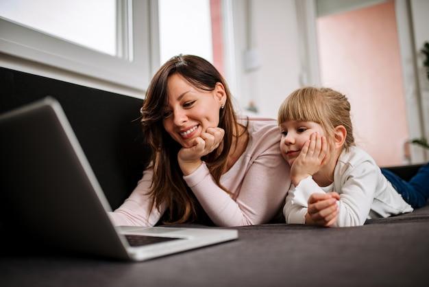 Jonge moeder en dochter kijken naar foto's op een laptop computer thuis.