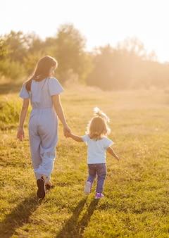 Jonge moeder en dochter, knuffelen en spelen in een gouden veld van zonneschijn