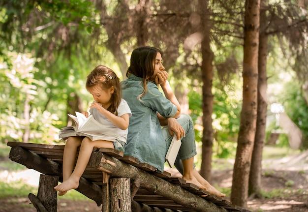 Jonge moeder en dochter lezen een boek in het park op een houten brug, het concept van een gelukkig gezinsleven en familierelaties