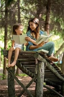 Jonge moeder en dochter lezen van een boek in het bos op een houten brug, het concept van een gelukkig gezinsleven en familierelaties