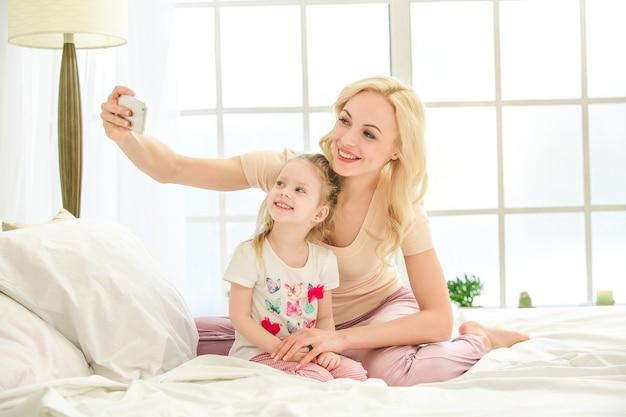Jonge moeder en dochter ochtend op bed binnenshuis
