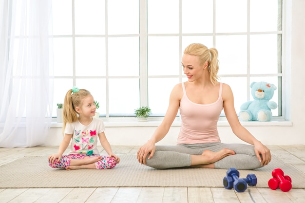 Jonge moeder en dochter oefenen samen binnenshuis