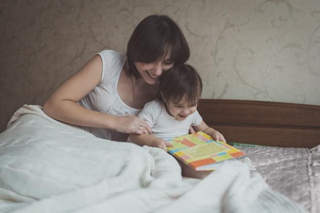 Jonge moeder en dochter peuter leesboek zittend op bed, levensstijl,